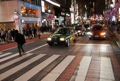 De bezige straat van Tokyo bij nacht met mensen die gestreepte manier kruisen Royalty-vrije Stock Foto's