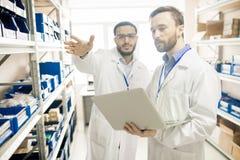 De bezige technici die van het fabriekslaboratorium verslagen van apparaten bijhouden stock afbeeldingen