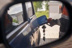 De bezinning in autospiegel van de man voorziet de auto op benzinepost van brandstof stock foto's