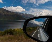 De bezinning van de autospiegel over weg door het meer royalty-vrije stock fotografie