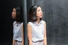 De bezinning van Aziatische jonge vrouw op de spiegel Royalty-vrije Stock Afbeelding
