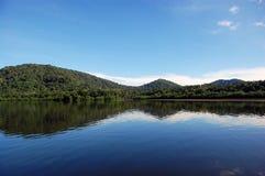 De bezinning van bergen bij rivierwaterspiegel Stock Foto