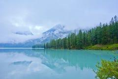 De bezinning van bergen en van pijnbomen in een ijzig meer stock afbeelding