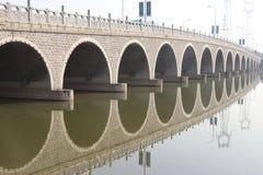 De bezinning van de brug in het water Stock Afbeelding