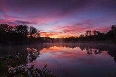 De bezinning van de ochtendzonsopgang over een meer Stock Foto's