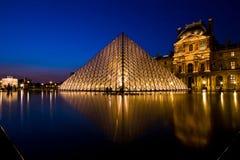 De bezinning van de piramide van het Louvre glanst bij schemer Stock Foto's