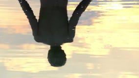 De bezinning van een Mediterende Mens wordt gezien in Meer bij een Schitterende Zonsondergang stock videobeelden