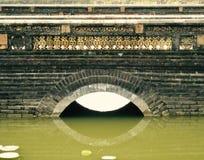De bezinning van een overladen steen en de baksteen overbruggen op een meer in Vietnam stock foto's