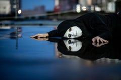 De bezinning van geheimzinnigheid hoodie de mens in wit maskergevoel drukte en stelde het liggen op natte vloer na de regen in te royalty-vrije stock afbeelding