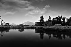 De Bezinning van het landschap over water in Zwart & Wit stock foto's