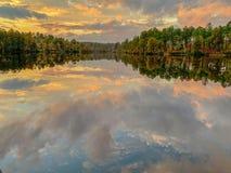 De bezinning van het spiegelmeer in daling met bomen en wolken stock fotografie