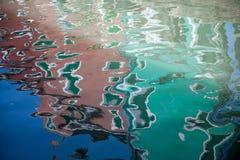 De bezinning van kleurrijke huizen in waterkanaal stock afbeeldingen