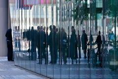 De bezinning van mensen in een modern gebouw Stock Foto