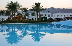 De bezinning van palmen in pool bij tropische zonsondergang Stock Foto's