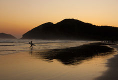 De Bezinning van Surfer en van de Zonsondergang bij een tropisch strand Stock Afbeeldingen