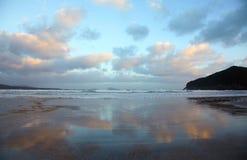 De bezinning van wolken in een nat zand Stock Fotografie