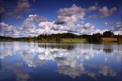 De bezinning van wolken in het meer stock foto
