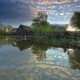 De bezinning van wolken in water met watermill Royalty-vrije Stock Afbeelding
