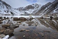 De bezinningen van de winter bij een bergmeer stock afbeelding