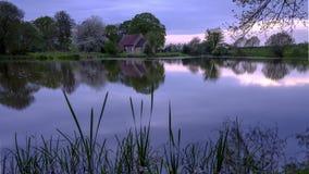 De bezinningen van St Leonard kerk in Hartley Mauditt Pond, Zuiden verslaat Nationaal Park, het UK stock foto