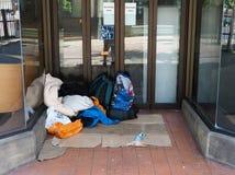 De bezittingen van een dakloze persoon in een winkeldeuropening royalty-vrije stock foto
