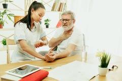De bezoekende verpleegster die de hogere mens behandelen royalty-vrije stock foto's