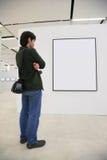 De bezoeker kijkt op frame in toonzaal stock foto's