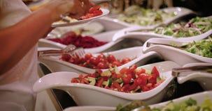 De bezoeker van restaurant zet salade in een plaat stock footage