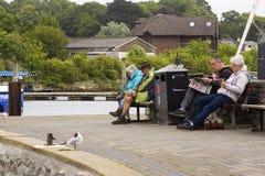 De bezoekers aan de kusttoevlucht van Lymington ontspannen op houten banken door de haven op een saaie koele dag stock foto's