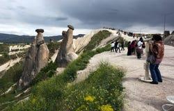 De bezoekers bewonderen feeschoorstenen dichtbij Urgup in het Cappadocia-gebied van Turkije stock foto