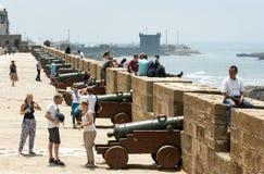 De bezoekers inspecteren een rij van canons bij de vroegere vesting in Essaouira in Marokko Stock Foto's