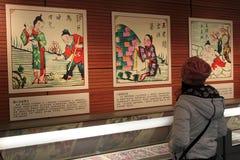 De bezoekers kijken schilderijen van het Nieuwjaar van China de traditionele op een tentoonstelling in de Nationale Bibliotheek va Royalty-vrije Stock Foto's