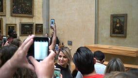 De bezoekers nemen foto van Leonardo DaVinci ` s ` Mona Lisa ` Louvre, Parise stock video