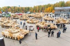 De bezoekers onderzoeken militaire voertuigen op tentoonstelling Royalty-vrije Stock Afbeeldingen