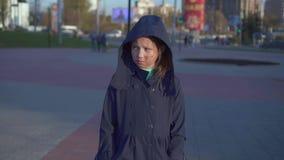 De bezorgde tiener met een tekort of het gezicht brandt op de straat met een kap lopend rond de stad stock video