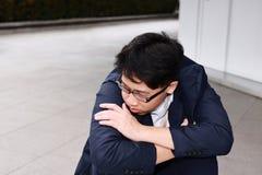 De bezorgdheid beklemtoonde de jonge Aziatische bedrijfsmens die aan streng probleem lijden royalty-vrije stock fotografie