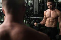 De Bicepsen van de jonge Mensenoefening met Domoren Stock Foto