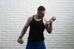 De Bicepsen van de jonge Mensenoefening met Domoren Royalty-vrije Stock Afbeelding