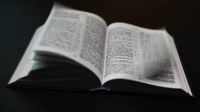 De Bijbel op een zwarte achtergrond Het draaien stock footage