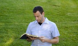 De Bijbel van de mensenlezing in het gras Stock Foto's