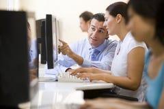 De bijwonende vrouw van de man in computerzaal Stock Foto