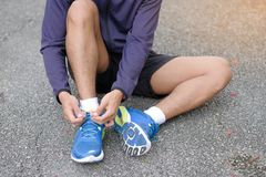 De bindende loopschoenen van de atletenmens in het park openlucht royalty-vrije stock fotografie