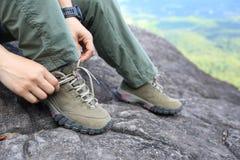 De bindende schoenveter van de vrouwenwandelaar op bergpiek Stock Afbeeldingen