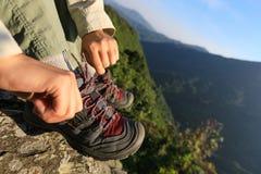 De bindende schoenveter van de vrouwenwandelaar op rand van de berg de hoogste klip Stock Afbeelding
