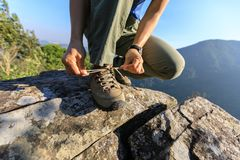 De bindende schoenveter van de vrouwenwandelaar op rand van de berg de hoogste klip Stock Foto