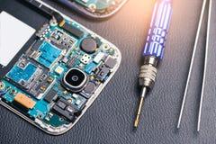 De binnenkant van motherboard van smartphone en de hulpmiddelen leggen op de achterlijst het concept computerhardware, mobiele te royalty-vrije stock fotografie