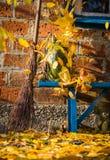 De binnenplaats van het de herfstdorp Pompoen, geel gebladerte en oude bezem op de achtergrond van een baksteenhuis royalty-vrije stock foto