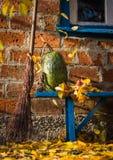 De binnenplaats van het de herfstdorp Pompoen, geel gebladerte en oude bezem op de achtergrond van een baksteenhuis stock afbeeldingen