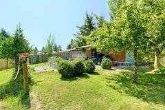De binnenplaats van het plattelandshuis met loods en tuin Stock Foto