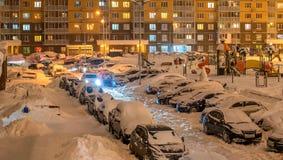 De binnenplaats van de de winteravond in woon complex behandeld met sneeuw en auto's Royalty-vrije Stock Fotografie